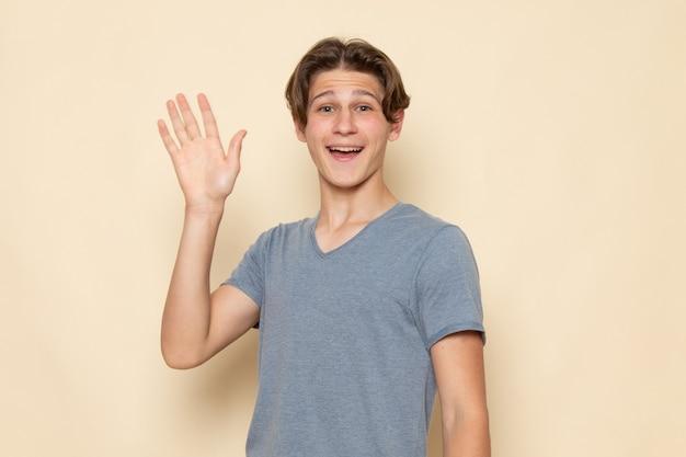 Ein junger mann der vorderansicht im grauen t-shirt, das seine hand mit lächeln winkend aufwirft