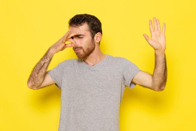 Ein junger mann der vorderansicht im grauen t-shirt, das seine nase auf dem farbmodell der gelben wandmannausdrucksemotion bedeckt