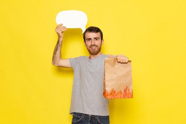 Ein junger mann der vorderansicht im grauen t-shirt, das weißes zeichen und paket mit lächeln auf dem gelben wandmannausdruck-emotionsfarbmodell hält