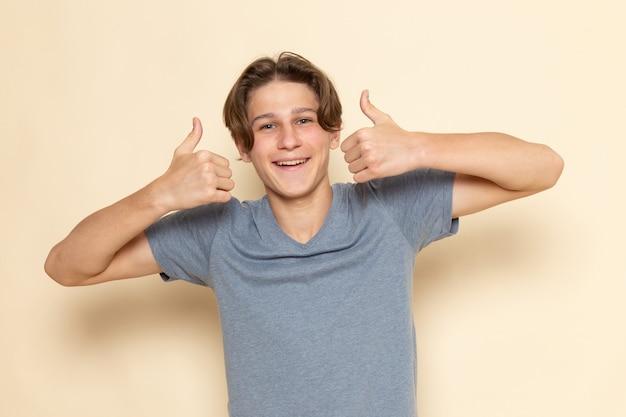 Ein junger mann der vorderansicht im grauen t-shirt, das wie zeichen mit lächeln zeigt