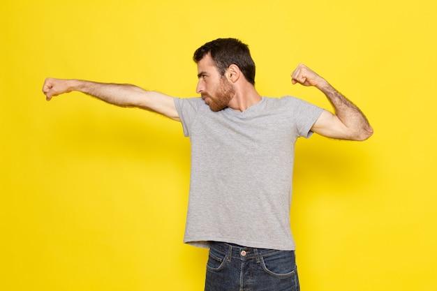 Ein junger mann der vorderansicht im grauen t-shirt, der einen tritt auf das gelbe wandmannausdruck-emotionsfarbmodell wirft