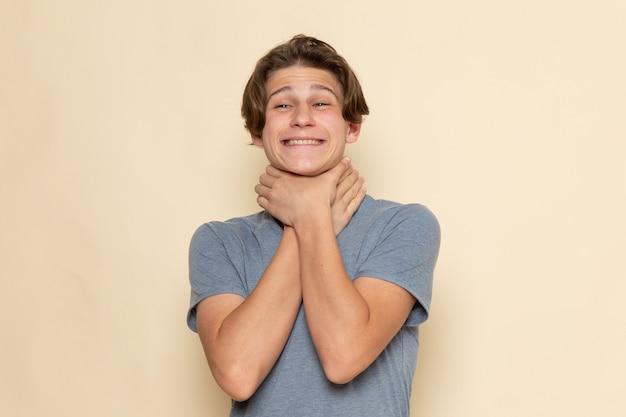 Ein junger mann der vorderansicht im grauen t-shirt, der sich erstickt