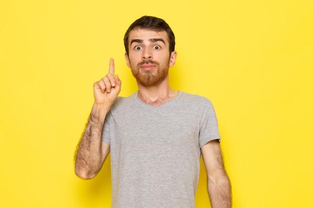 Ein junger mann der vorderansicht im grauen t-shirt mit einem ideenausdruck auf dem farbmodell der gelben wandmannausdrucksemotion