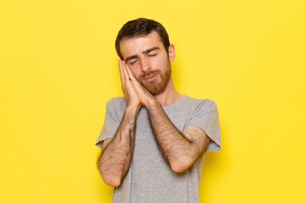 Ein junger mann der vorderansicht im grauen t-shirt mit schlafender haltung auf dem gelben wandmannfarbmodell