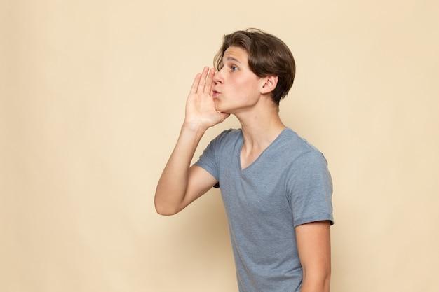 Ein junger mann der vorderansicht im grauen t-shirt ruft heraus
