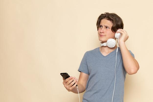 Ein junger mann der vorderansicht im grauen t-shirt unter verwendung des telefons, das musik hört