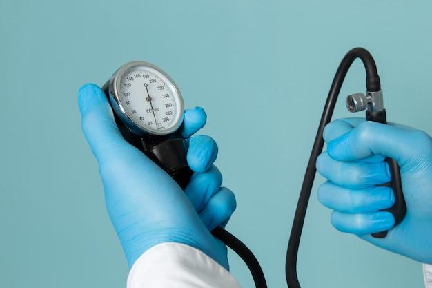 Ein junger mann der vorderansicht im weißen hemd und in den blauen handschuhen, die stethoskop auf dem blauen raum halten