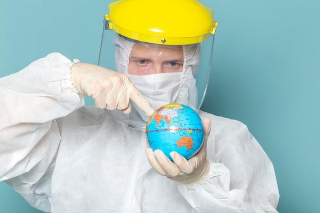 Ein junger mann der vorderansicht im weißen sonderanzug und im gelben sonderhelm, der globus auf der blauen wandmannanzug-gefahrenausrüstungsausrüstungsfarbe hält