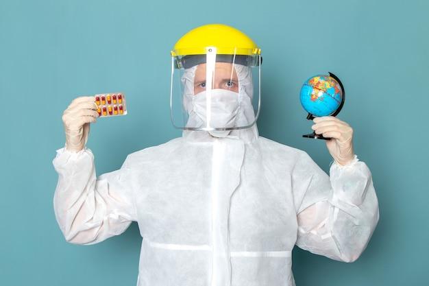 Ein junger mann der vorderansicht im weißen sonderanzug und im gelben sonderhelm, der kleinen globus und pillen auf der blauen wandmannanzug-sonderausrüstungsfarbe hält