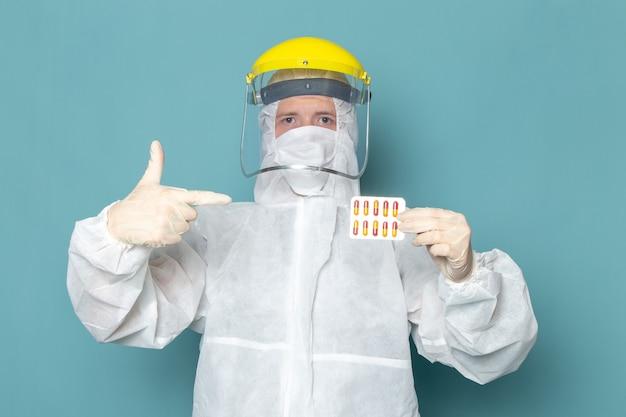 Ein junger mann der vorderansicht im weißen sonderanzug und im gelben spezialhelm, der pillen auf der blauen wandmannanzug-sonderausrüstungsfarbe hält