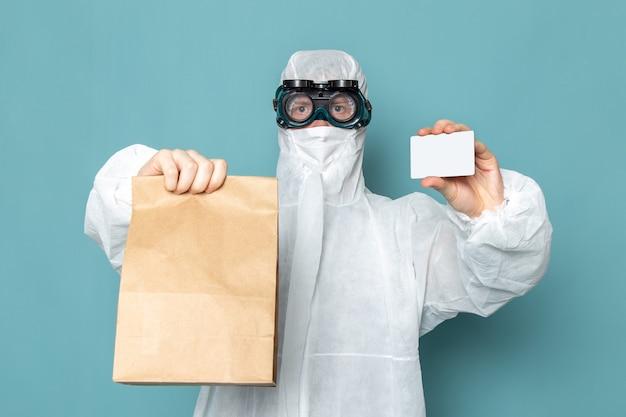 Ein junger mann der vorderansicht im weißen sonderanzug und im halten der weißen karte und des pakets auf der blauen wandmannanzuggefährdungsausrüstungsfarbe