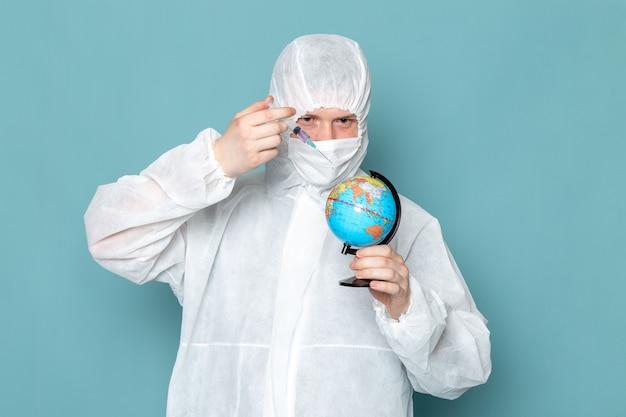 Ein junger mann der vorderansicht im weißen sonderanzug und im halten des kleinen globus auf der blauen wandmannanzuggefahr-sonderausrüstungsfarbe