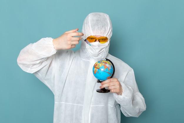 Ein junger mann der vorderansicht im weißen sonderanzug und im halten und spritzen des kleinen globus auf der blauen wandmannanzuggefahr-sonderausrüstungsfarbe