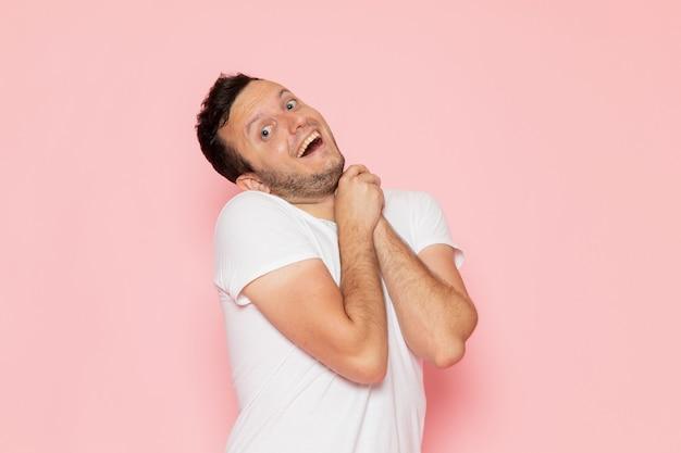 Ein junger mann der vorderansicht im weißen t-shirt, das mit aufgeregtem ausdruck aufwirft