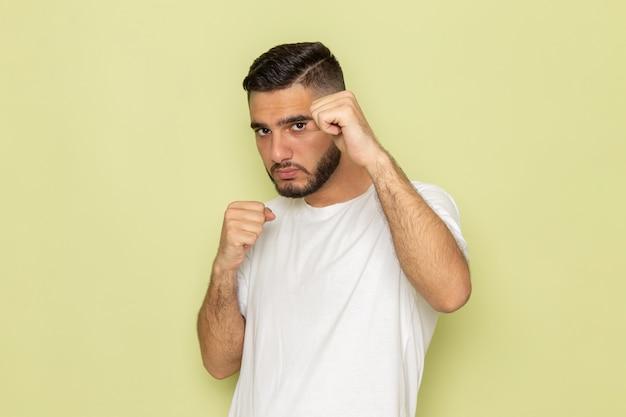 Ein junger mann der vorderansicht im weißen t-shirt, das mit boxständer aufwirft