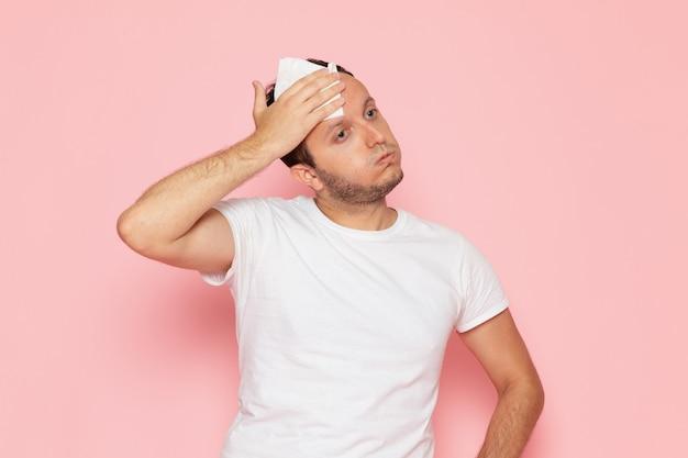 Ein junger mann der vorderansicht im weißen t-shirt, das mit dem müden ausdruck aufwirft