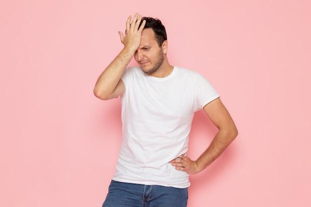 Ein junger mann der vorderansicht im weißen t-shirt, das mit enttäuschtem ausdruck aufwirft