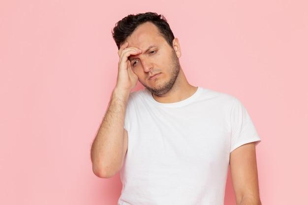Ein junger mann der vorderansicht im weißen t-shirt, das mit gestresstem ausdruck aufwirft