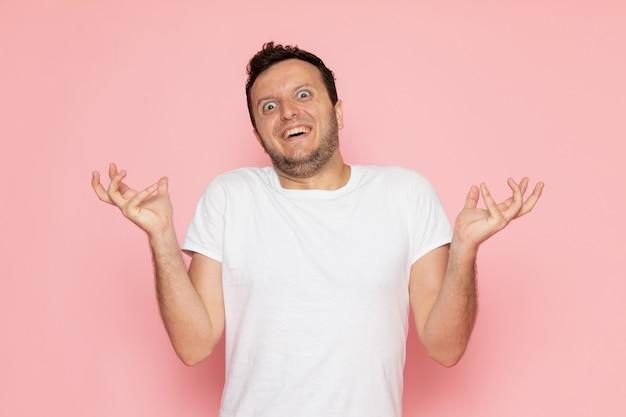 Ein junger mann der vorderansicht im weißen t-shirt, das mit lustigem ausdruck aufwirft