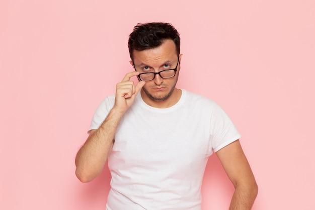 Ein junger mann der vorderansicht im weißen t-shirt, das mit optischer sonnenbrille aufwirft