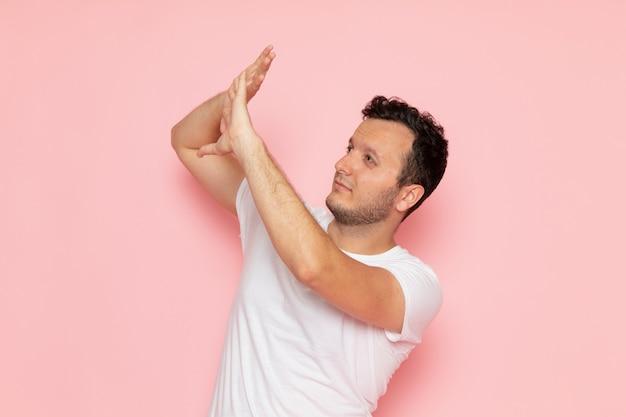 Ein junger mann der vorderansicht im weißen t-shirt, das mit vorsichtigem ausdruck aufwirft