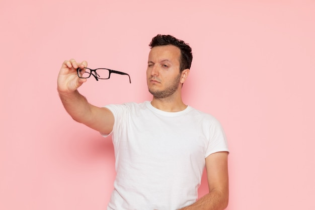 Ein junger mann der vorderansicht im weißen t-shirt, das optische sonnenbrille hält