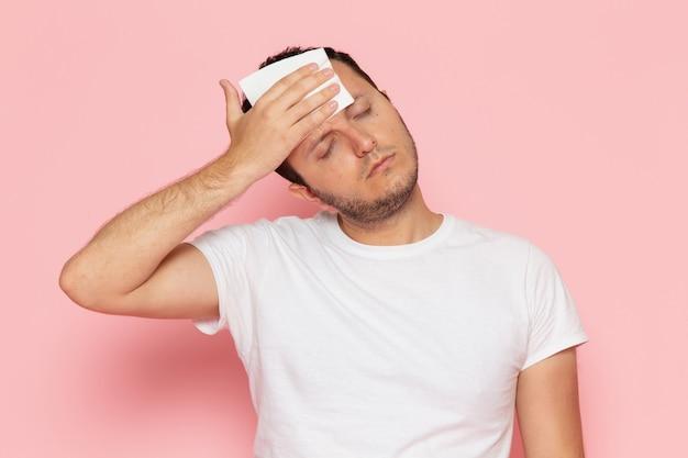 Ein junger mann der vorderansicht im weißen t-shirt, das seine stirn reibt