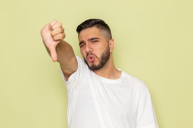 Ein junger mann der vorderansicht im weißen t-shirt, das unähnliches zeichen zeigt