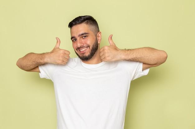 Ein junger mann der vorderansicht im weißen t-shirt, das wie zeichen mit lächeln zeigt