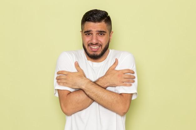 Ein junger mann der vorderansicht im weißen t-shirt, das zittert