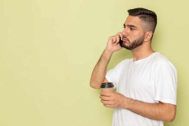 Ein junger mann der vorderansicht im weißen t-shirt, der kaffee hält, der am telefon spricht
