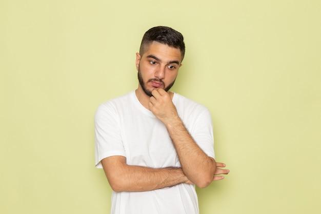 Ein junger mann der vorderansicht im weißen t-shirt, der tief nachdenkend ist