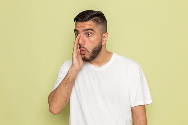 Ein junger mann der vorderansicht im weißen t-shirt flüstert