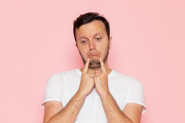 Ein junger mann der vorderansicht im weißen t-shirt mit dem traurigen ausdruck auf der farbemotionshaltung der rosa schreibtischmannfarbe