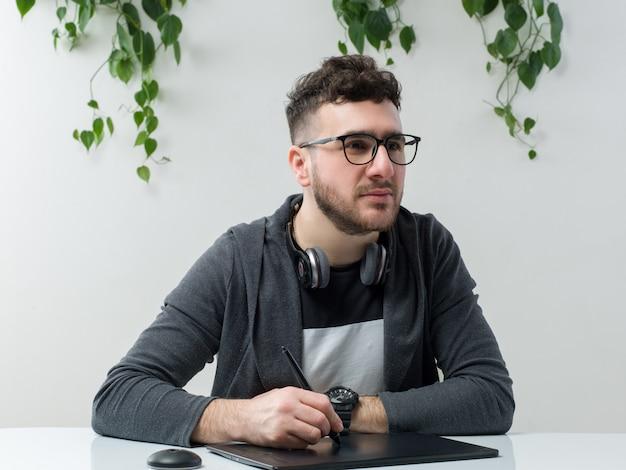 Ein junger mann der vorderansicht in der sonnenbrille, die zusammen mit laptop auf dem weißen raum sitzt