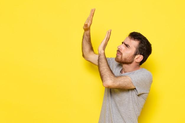 Ein junger mann der vorderansicht in grauem t-shirt mit ängstlichem ausdruck auf dem gelben wandmannausdruck-emotionsfarbmodell