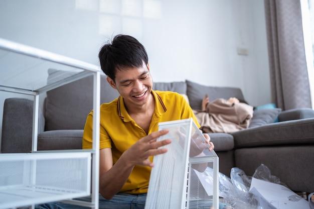 Ein junger mann, der zu hause im wohnzimmer ein regal aufbauen möchte.