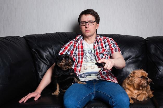 Ein junger mann, der zu hause mit hunden fernsieht.