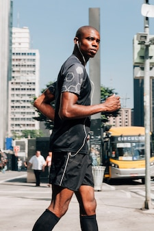 Ein junger mann des überzeugten männlichen athleten, der auf der straße hörend die musik auf kopfhörer rüttelt