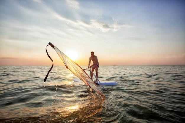 Ein junger mann, ein athlet wirft ein segel auf einem windsurf
