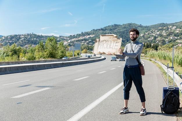 Ein junger mann fährt per anhalter, steht auf der autobahn mit einem schild.