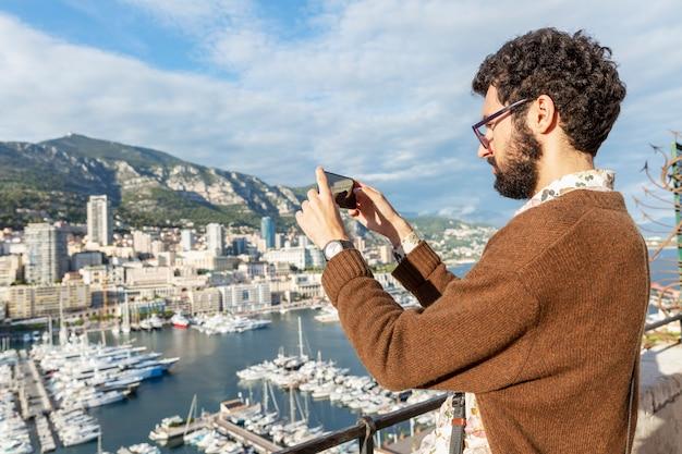 Ein junger mann fotografiert einen schönen blick auf den yachthafen an einem sonnigen tag.