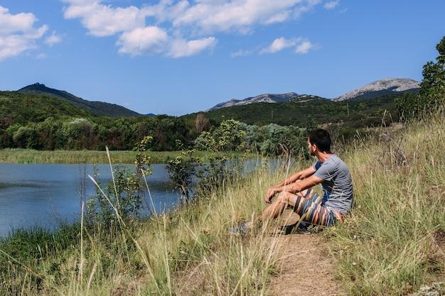 Ein junger mann geht alleine am see mit einer berglandschaft spazieren