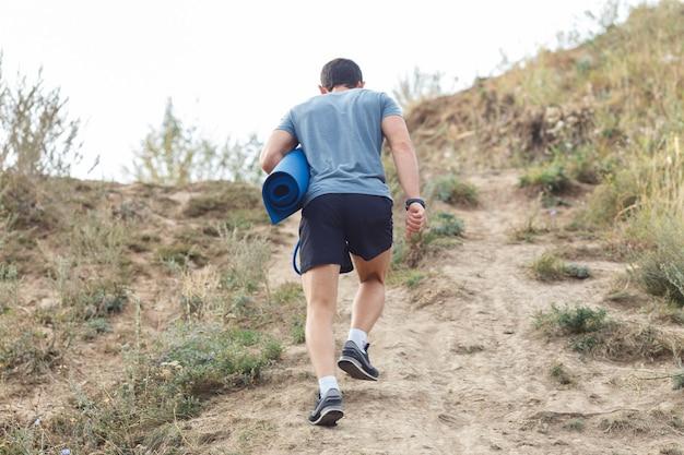 Ein junger mann geht auf den spuren. reisesport-lifestyle-konzept. blick von hinten
