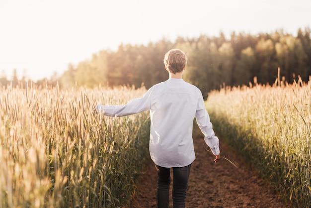 Ein junger mann geht im sommer auf das feld. blick von hinten