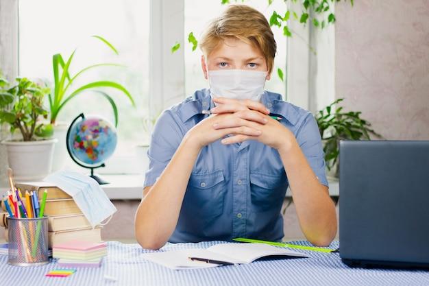 Ein junger mann, gekleidet in ein blaues hemd und eine maske, sitzt mit verschränkten armen an einem schreibtisch. pandemie. bildungskonzept.
