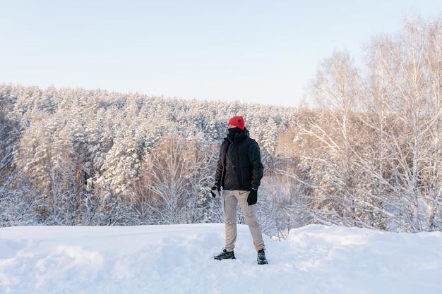 Ein junger mann genießt einen wintertag vor dem hintergrund eines schneebedeckten waldes