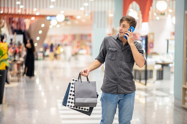 Ein junger mann hält viele pakete vom einkaufen in der hand, ich gehe durch das einkaufszentrum, telefoniere und schaue zur seite. einkaufskonzept. schwarzer freitag.