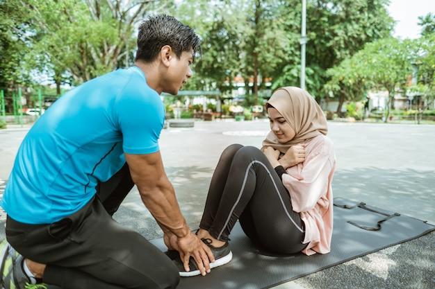Ein junger mann hilft dabei, die beine eines verschleierten mädchens zu halten, das beim outdoor-sport im park bauchmuskeltraining macht