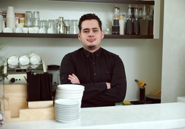 Ein junger mann hinter der bar posiert
